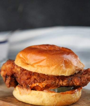 popeye's fried chicken sandwich on a wooden board.