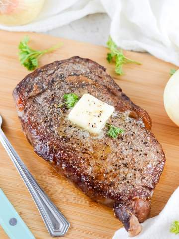 air fryer cooked steak with butter and parsley on top.