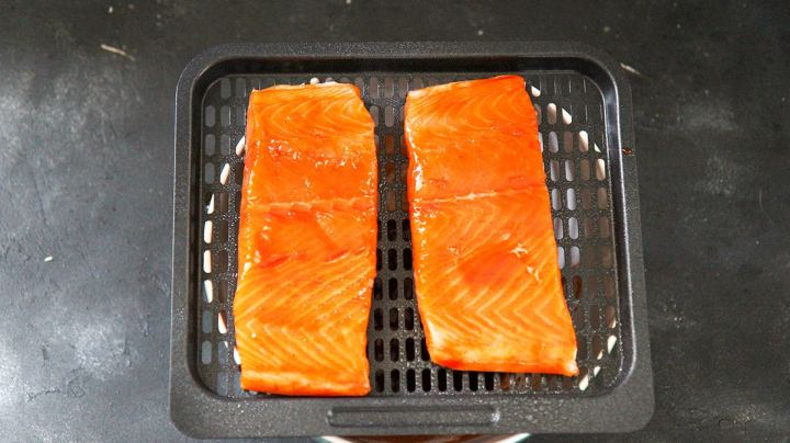two raw salmon fillets on the air fryer basket.