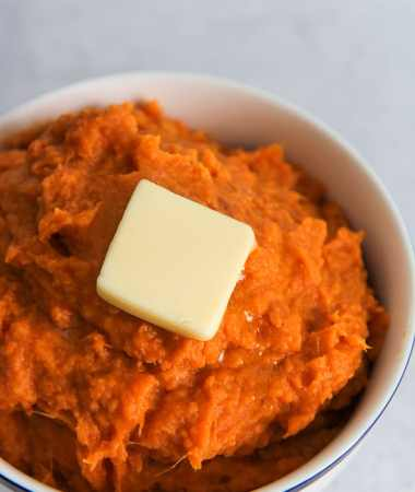 a small white bowl filled with mashed sweet potatoes and a slice of butter on top.