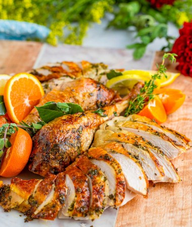 cooked turkey sliced and decorated with oranges and fresh herbs.
