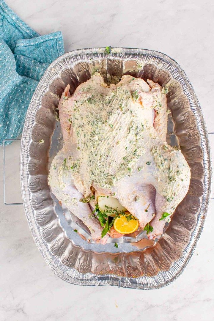raw turkey smothered with softened butter and herbs inside a baking dish.