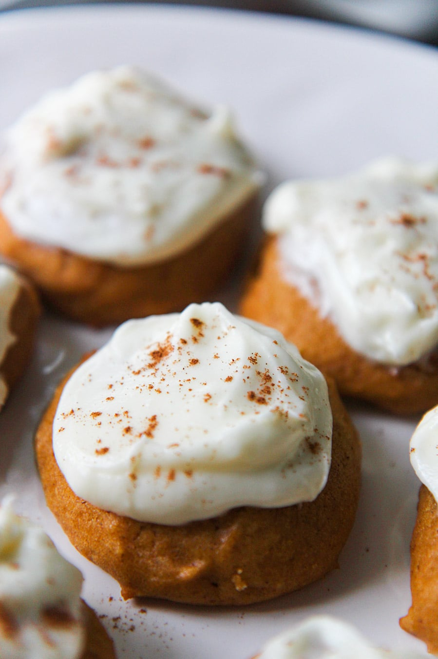 pumpkin cookies with cream cheese frosting and cinnamon on top.