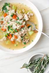 leftover turkey and rice soup in a white bowl with fresh rosemary on the side.