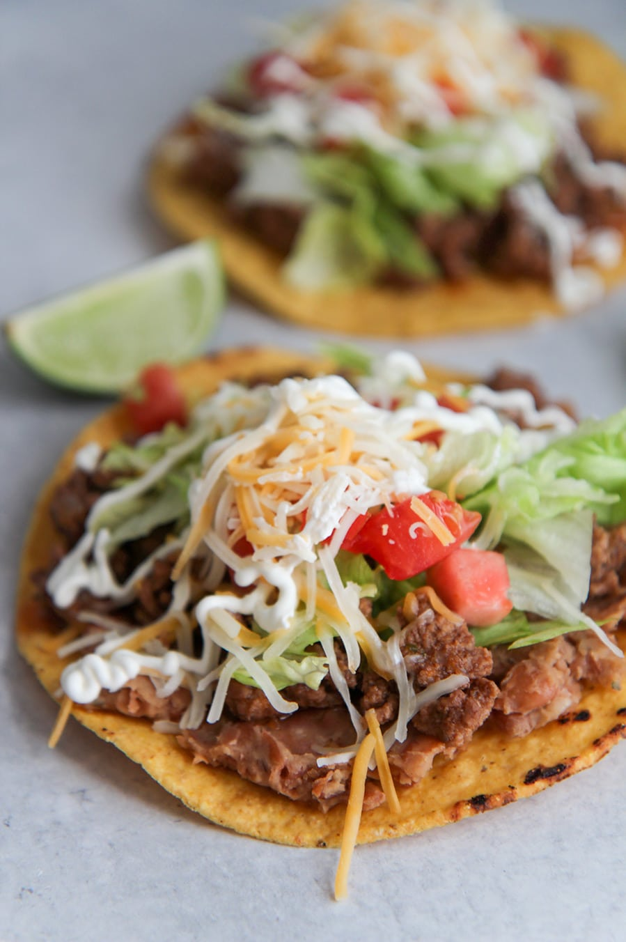 two beef tostadas with refried beans, lettuce, tomatoes, cheese, sour cream, and limes on the side.