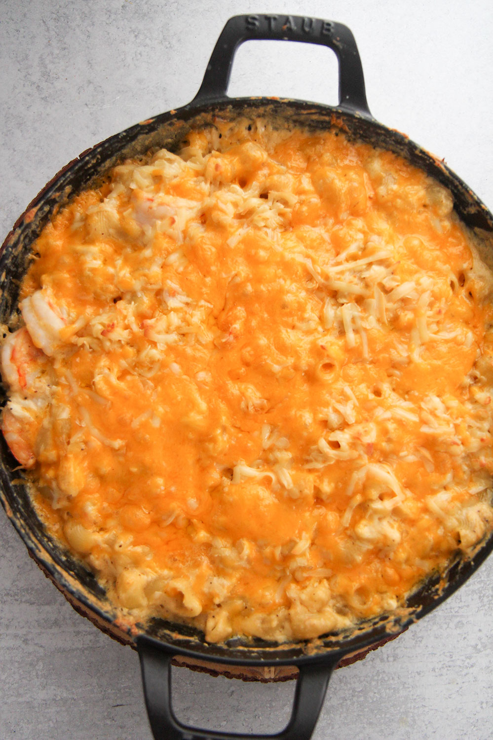 seafood macaroni and cheese in a black cast iron skillet.
