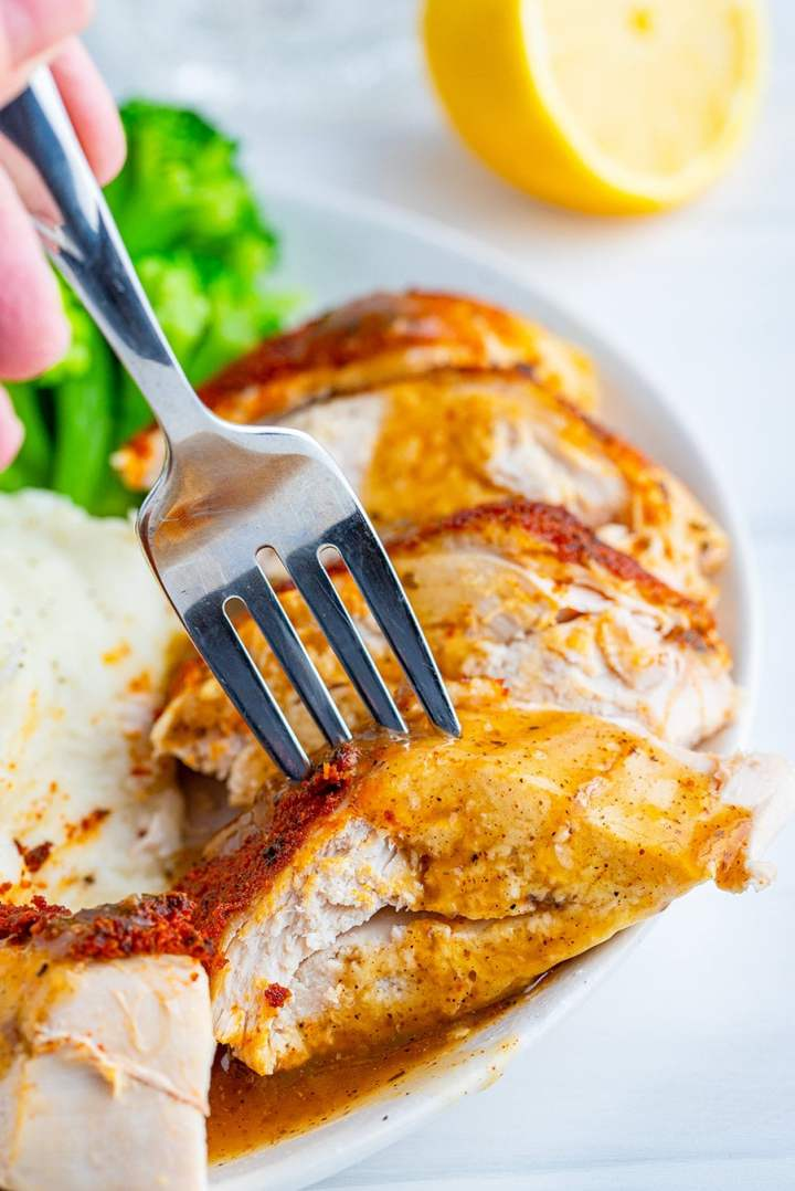 sliced chicken breast with a fork and gravy.