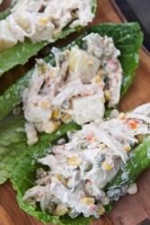 ensalada de pollo (chicken salad) on three lettuce cups.