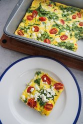a slice of spinach and goat cheese frittata on a white and blue plate with a 9x13 frittata in the background.