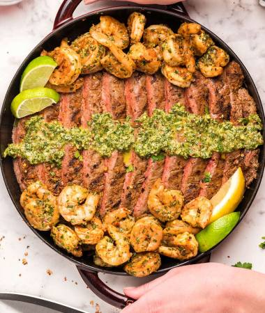 steak, shrimp, and chimichurri, on a grill.