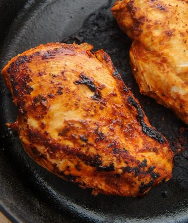 two chipotle chicken breasts in a cast iron skillet.