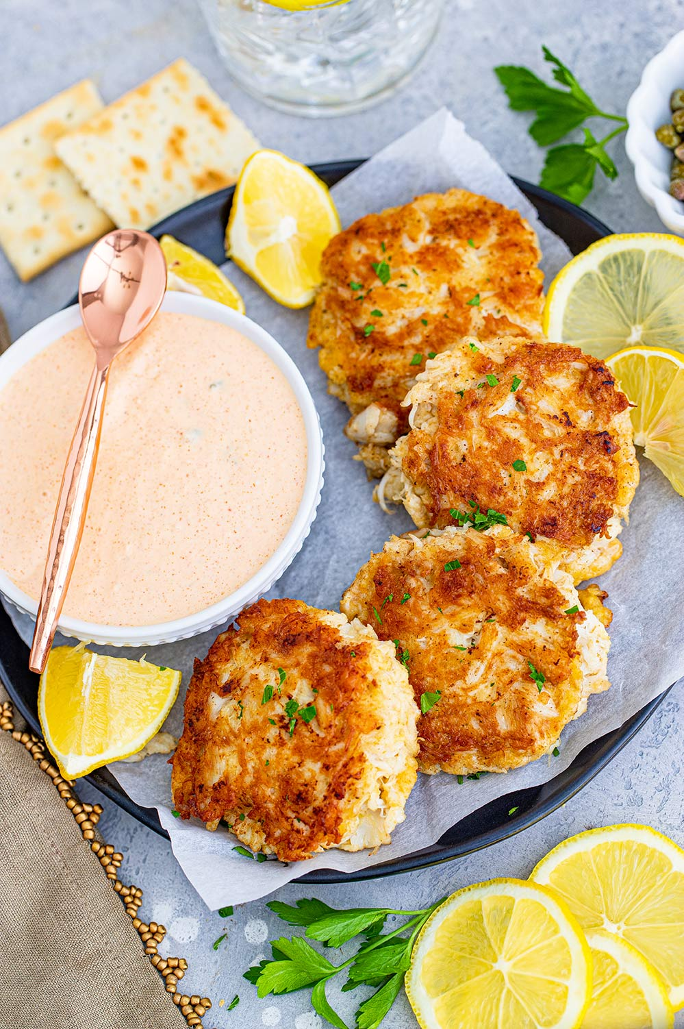 four crab cakes on a plate with a side of remoulade sauce and lemon wedges.