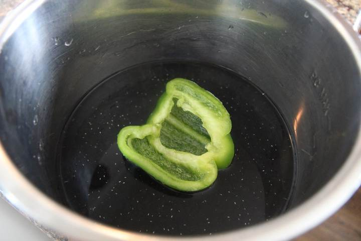 Black dried beans, water, and a green bell pepper in a pot.