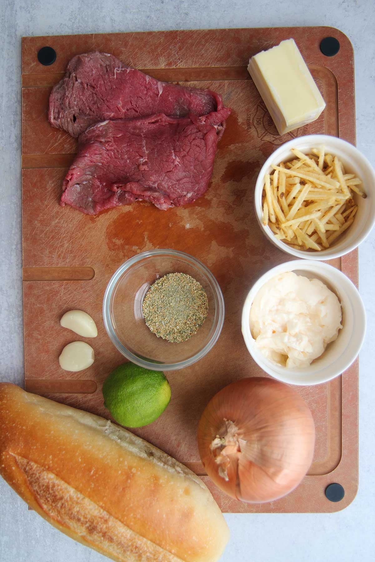 ingredients for pan con bistec. Spices in a small bowl, mayo in a bowl, steaks, lime, garlic, onion, butter, and potato straws.