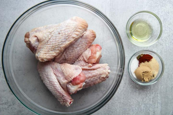 raw turkey wings in a glass bowl and spices and oil in two small bowls.