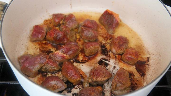 beef browning in a white pot.
