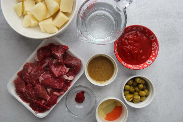 raw beef chunks, tomato sauce, olives, potatoes, spices, sofrito, and water.