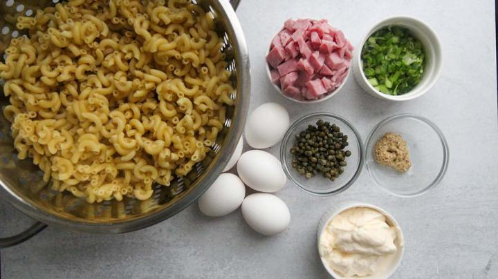 macaroni pasta, eggs, capers, ham, scallions, mayo and mustard in small bowls.