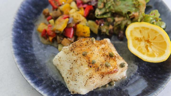 Cooked fish with capers and lemon butter sauce on top.
