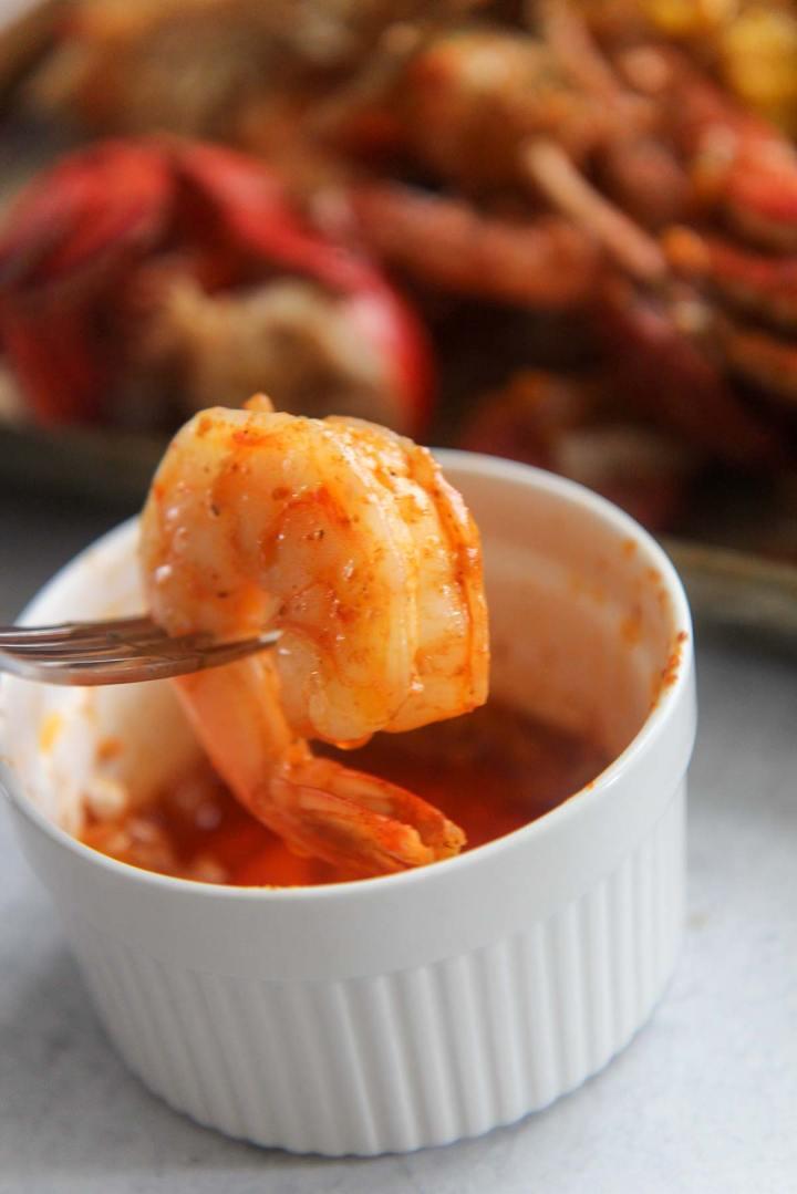 Shrimp dipped in seafood boil sauce.