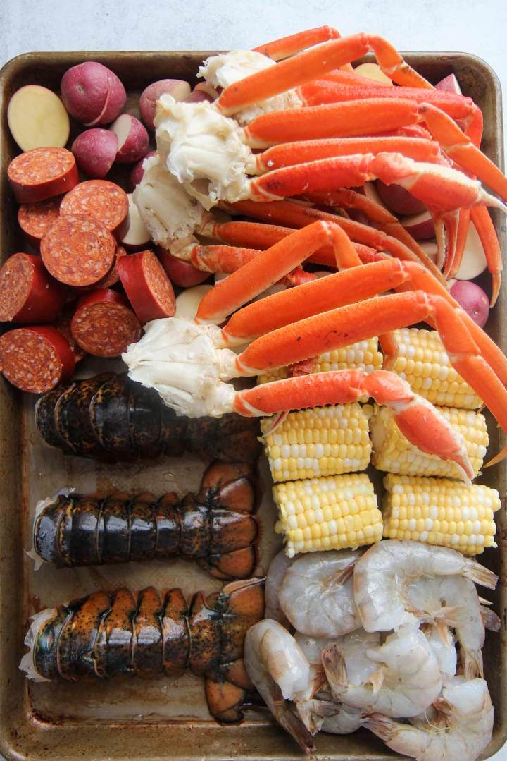 ingredients for seafood boil. Raw shellfish, corn, potatoes, and sausage.