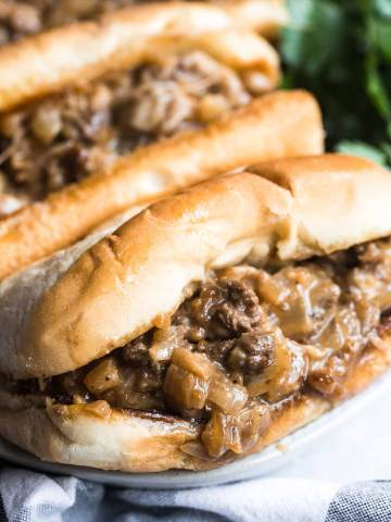 Two Philly cheesesteak sandwiches up close.