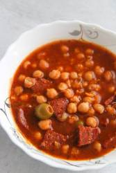 Garbanzos guisados in a white bowl up close.
