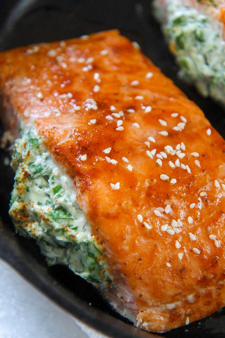 spinach stuffed salmon in a cast iron skillet.