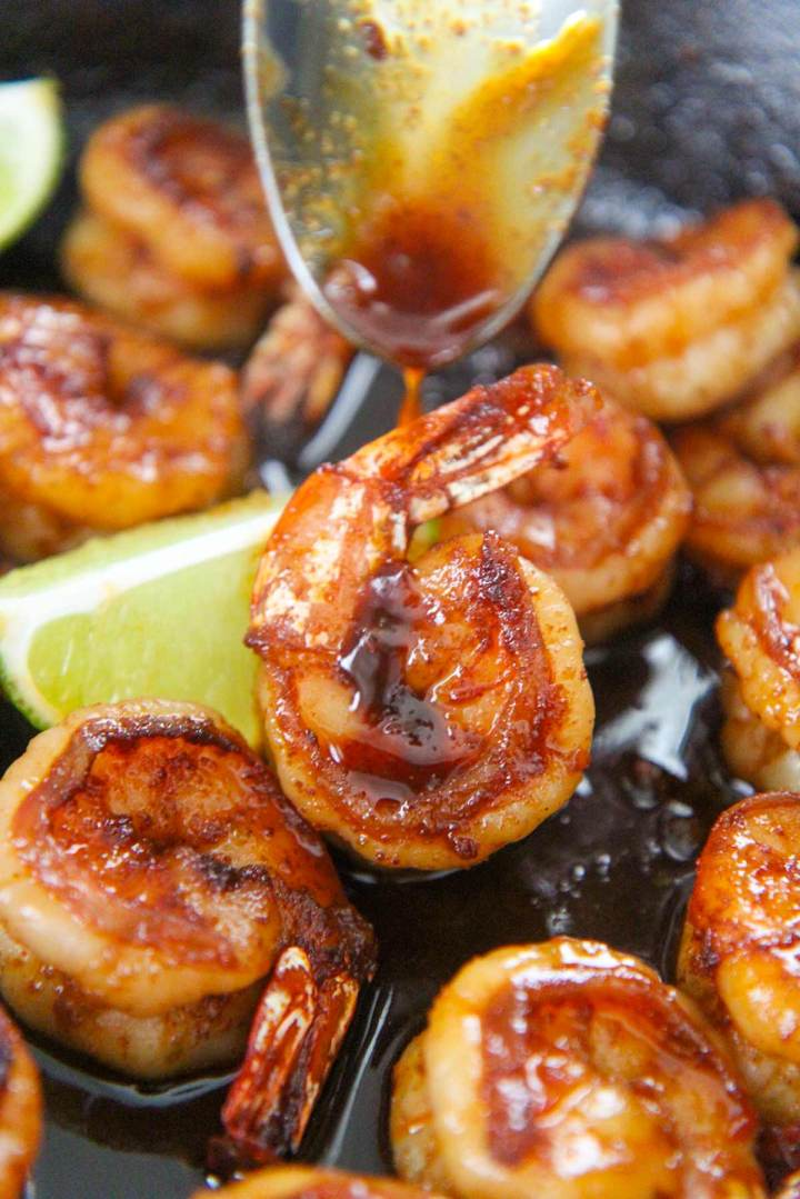 honey chili lime shrimp up close with a spoon drizzling sauce on top.