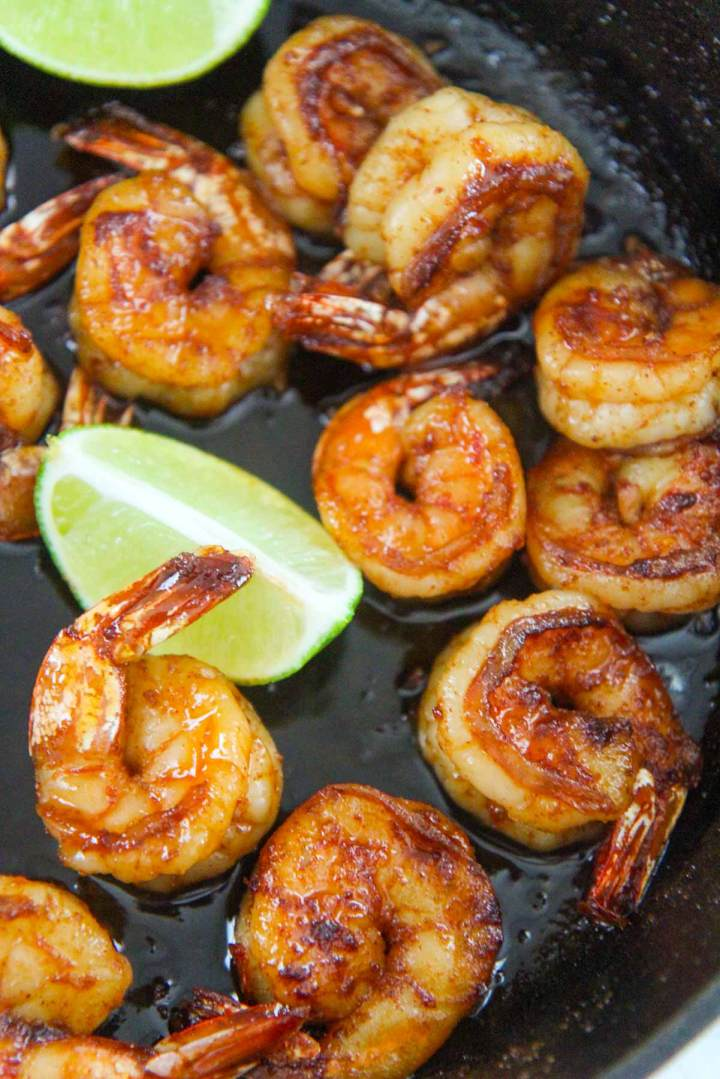 cooked shrimp in a skillet with lime wedges.