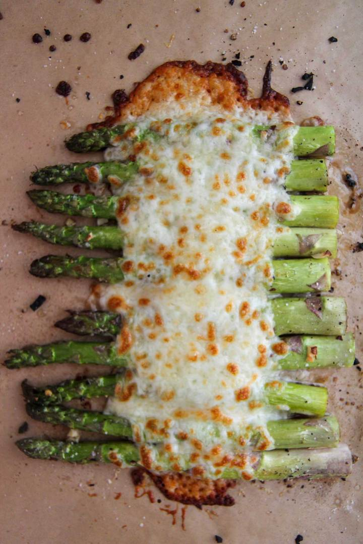 cheesy garlic asparagus on a baking sheet.