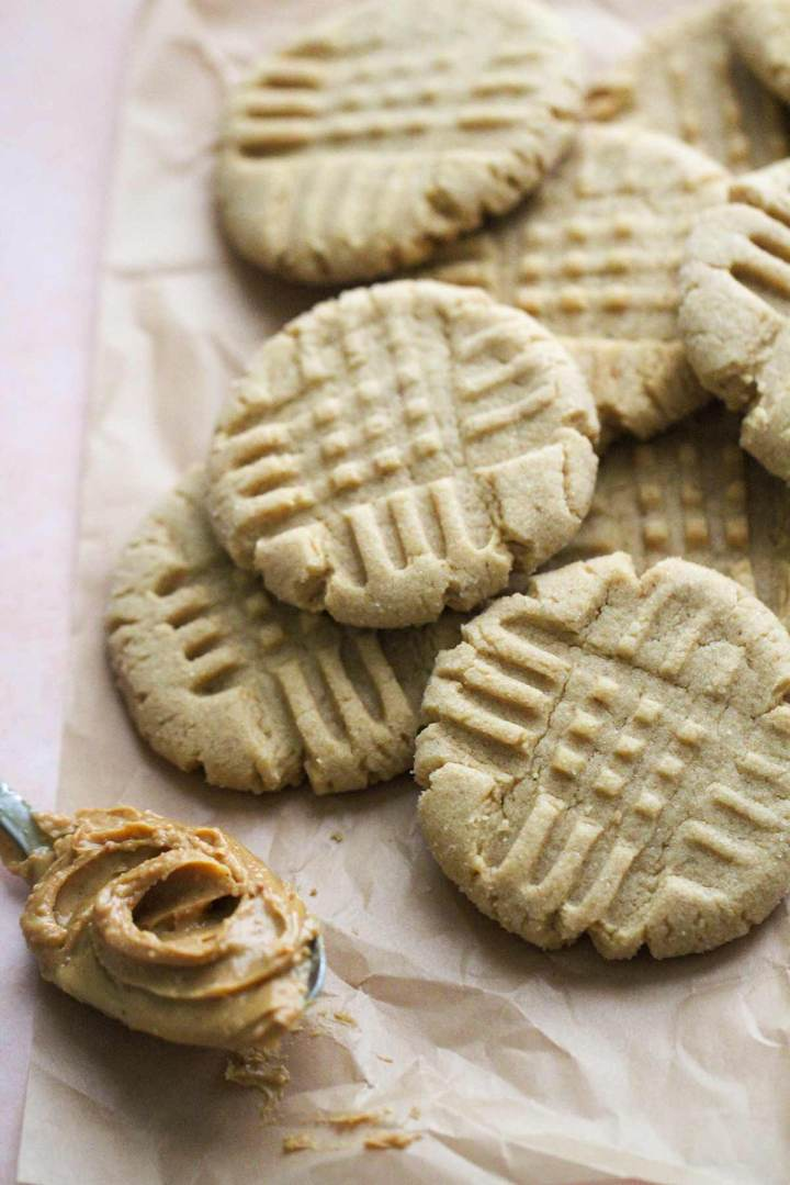 peanut butter cookies on top of parchment paper with a spoonful of peanut butter on the side.