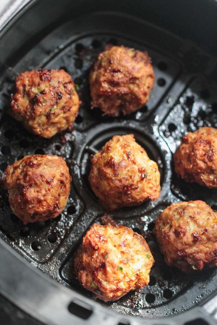 seven turkey meatballs in the air fryer basket.