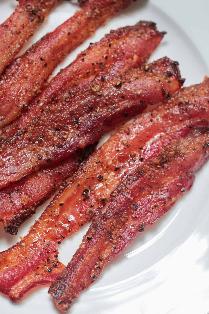 cooked candied bacon on a white plate.