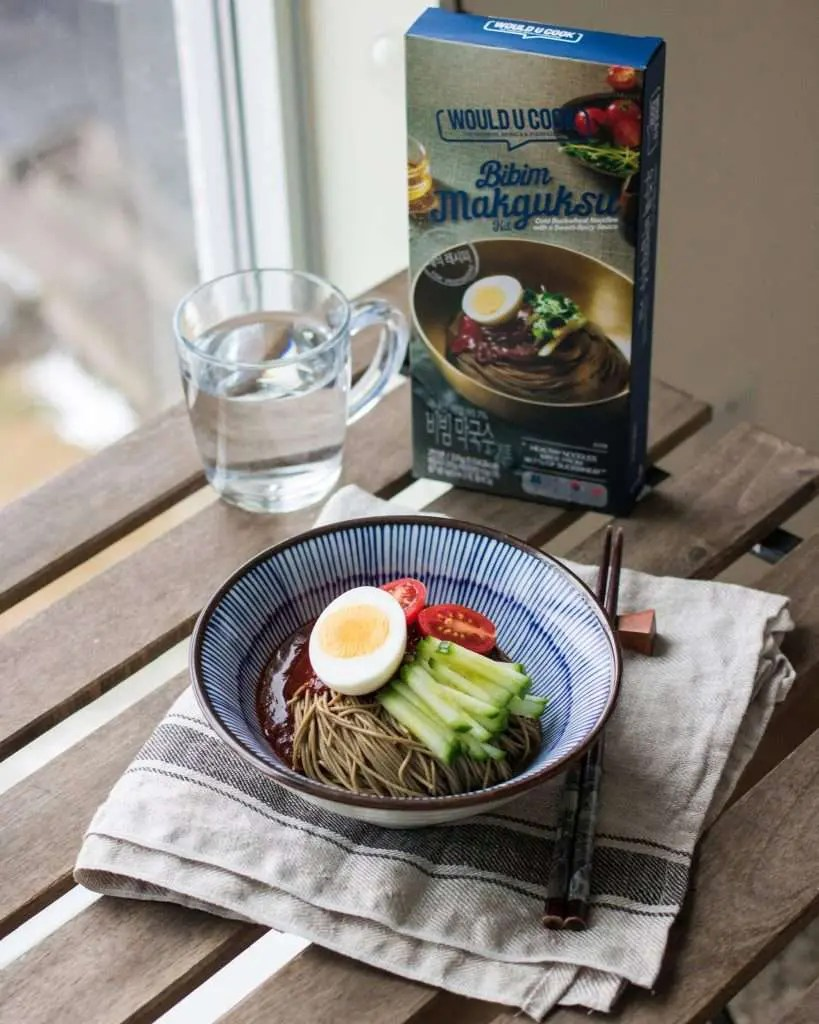 bibim makguksu korean cold noodles served in a bowl with woulducook meal kit in the background