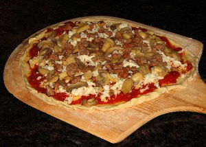Suasage, Mushroom, Caramelized Onion Pizza ready for oven