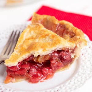square image of a slice of pie on a white plate with a fork