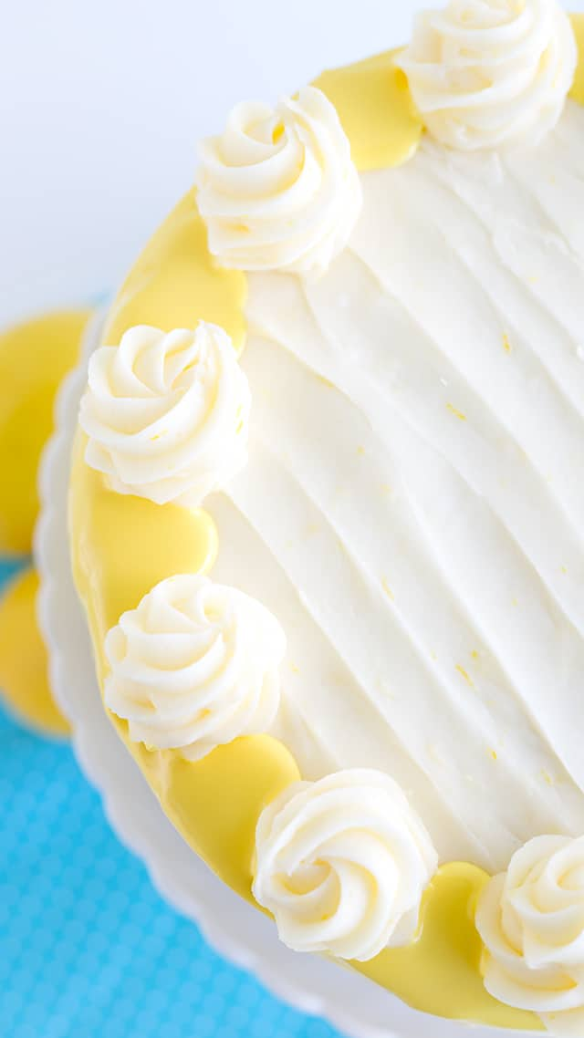 looking down onto the top of a lemon olive oil cake with swirls of cream cheese frosting on top