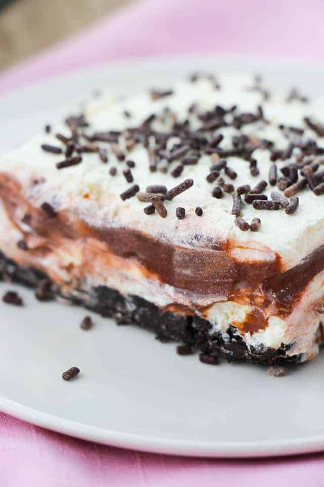Upclose picture of the front of a slice of chocolate layer dessert on a white plate