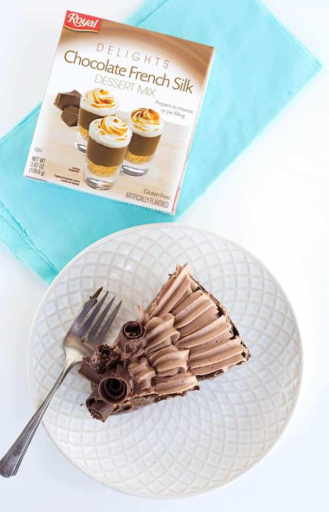 overhead shot of a slice of the chocolate cream pie on a white plate with a box of Royal Delights dessert mix sitting on a piece of blue fabric beside it.