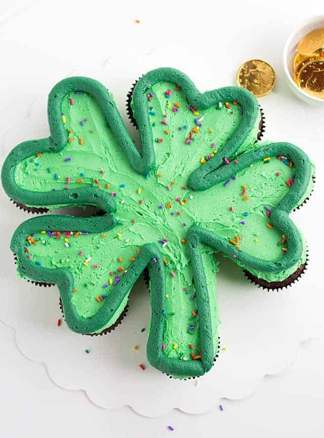 A green shamrock cupcake cake on a white cake board with gold chocolate coins scattered.