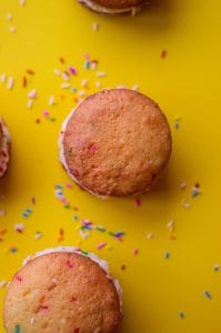 overhead of funfetti cake mix whoopie pies with yellow background and sprinkles scattered