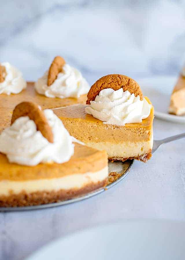 serving a slice of double layer pumpkin cheesecake