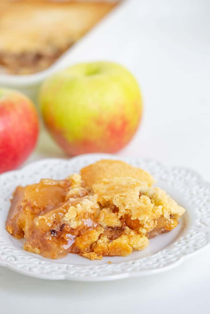 plate full of dump cake with apples behind it and a baking pan