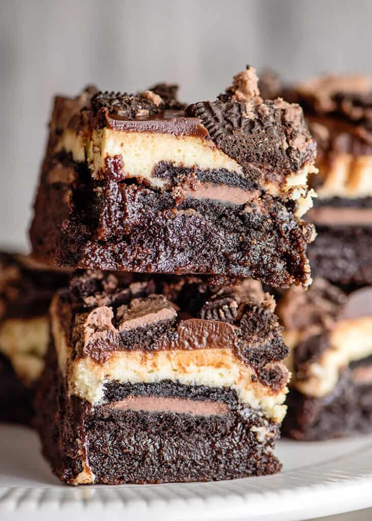 stack of brownie bars on a white surface