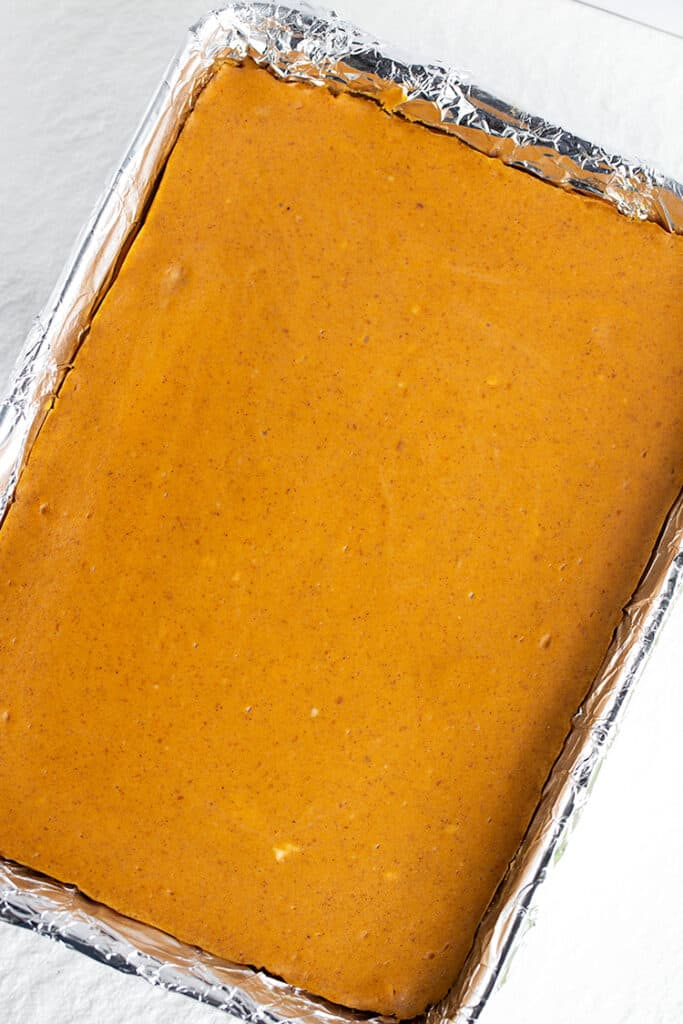 pan of pumpkin cheesecake bars with a white surface