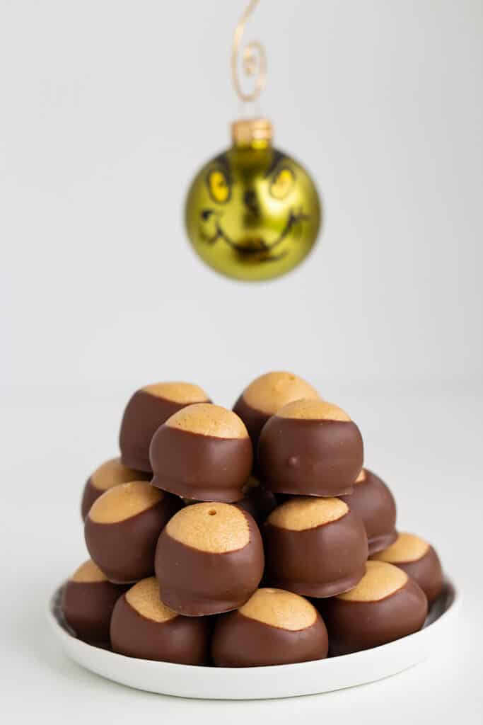 stack of peanut butter balls with a grinch ornament hanging behind it