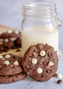 cookie propped up against a glass of milk on a marble background
