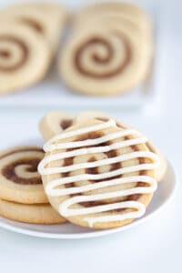 glazed cinnamon roll cookie on a white plate with other cookies behind it