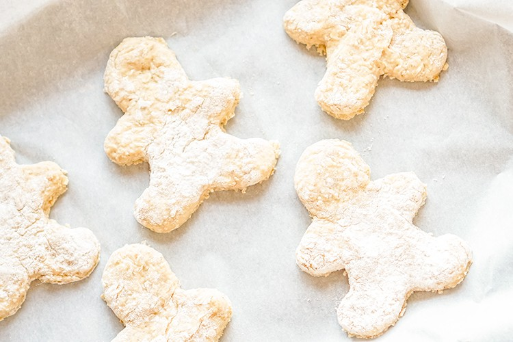 gingerbread man dog treats on a parchment lined cookie sheet